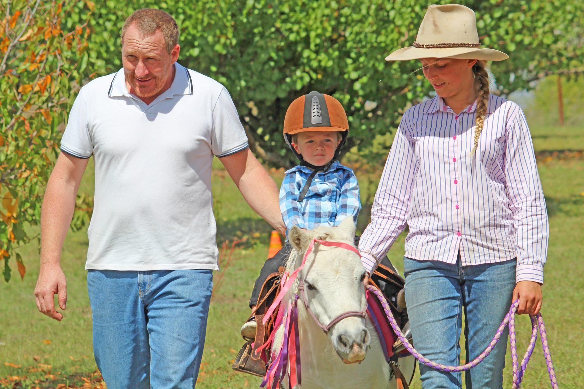 Boy Riding Pony With Dad