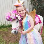 Girl In Rainbow Dress Hugging Pony